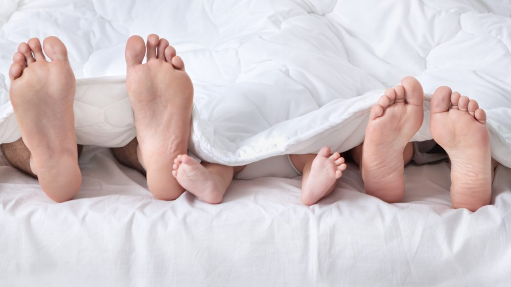 Feet of a family sticking out from the white quilt